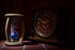 Het concept van de tijd Silhouet van Zandloperklok en oude uitstekende houten klok met pijl en rook op donkere achtergrond met he Royalty-vrije Stock Foto's