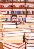 Het Concept van de tijdstroom De mens op verrast gezicht houdt zandloper terwijl het bestuderen, boekenrekken op achtergrond Lera stock afbeelding