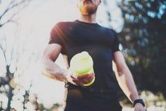 Het concept van de traininggeschiktheid Spier gebaarde atleet met eiwitmilkshakecocktail na harde trainingzitting over stad stock foto