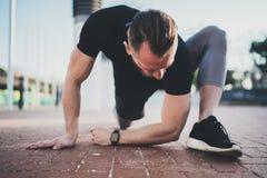 Het concept van de traininglevensstijl De jonge mens die rek doen oefent spieren uit alvorens op te leiden Spieratleet die buiten royalty-vrije stock foto
