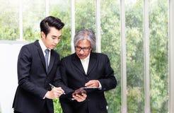 Het concept van de vergadering Twee Aziatische zakenman iscussing documenten dienen bureau in royalty-vrije stock afbeeldingen