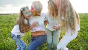 Het concept van de vriendschap Jonge gelukkige vrouwen met hun dochters die pret hebben die vervenholi werpen stock videobeelden