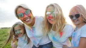 Het concept van de vriendschap Jonge gelukkige vrouwen met hun dochters die pret hebben die vervenholi werpen stock video