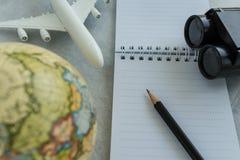 Het concept van de wereldreis met potlood op wit notadocument, stuk speelgoed airpla Stock Foto's