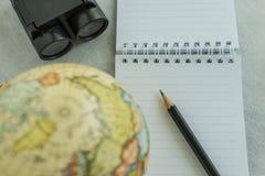 Het concept van de wereldreis met potlood op wit notadocument, verrekijkers Stock Foto