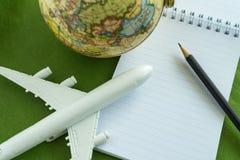 Het concept van de wereldreis met stuk speelgoed vliegtuig, potloodnota en bol  Royalty-vrije Stock Afbeelding