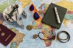 Het concept van de wereldreis met voorwerpen bovenop kaart Stock Afbeeldingen