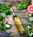 Het concept van de wijn Fles en glas jonge witte biowijn met groene druiven, grapefruit en ander fruit op een oude houten lijst stock foto's