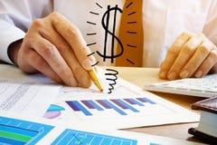 Het concept van de winst De tekens van de calculator en van de dollar Het van bedrijfs zakenmanAnalyze verdienen royalty-vrije stock foto
