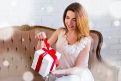 Het concept van de de wintervakantie - verraste mooie vrouw het openen gift Stock Afbeeldingen