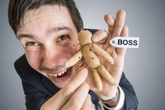 Het concept van de wraak Jonge werknemer en voodoopop met Chef- etiket Royalty-vrije Stock Afbeelding