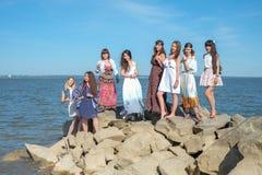Het concept van de de zomervakantie - de groep glimlachende jonge vrouwen rust op de kust Stock Fotografie