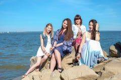 Het concept van de de zomervakantie - de groep glimlachende jonge vrouwen rust op de kust Royalty-vrije Stock Fotografie