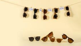 Het concept van de zonnebrilverkoop Verschillende zonnebril die op de kabel met uitdrukkingspret hangen in de zon op gele achterg stock fotografie