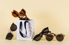 Het concept van de zonnebrilverkoop Verschillende zonnebril in het shoping van zakken op gele achtergrond De toebehoren van de ma stock foto