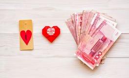 Het concept van het geld pak van Chinese munt op wit rustiek achtergrond woth origamihart Royalty-vrije Stock Foto's