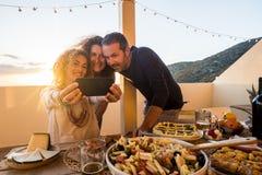 Het concept van groeps mensen friednship heeft pret die samen selfie tijdens een diner of een lunch thuis openlucht in het terras royalty-vrije stock afbeeldingen