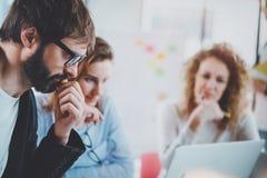 Het concept van het groepswerkproces jonge medewerkers die met nieuw startproject op zonnig kantoor werken Horizontale, vage acht royalty-vrije stock afbeeldingen
