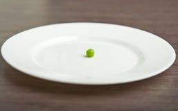 Het concept van het dieet. één erwt op een lege witte plaat Royalty-vrije Stock Foto
