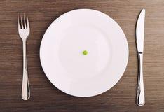 Het concept van het dieet. één erwt op een lege witte plaat Stock Foto