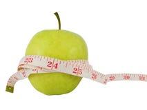 Het concept van het dieet met een groene appel en een maatregelenband Stock Afbeelding
