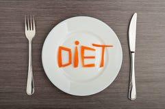 Het concept van het dieet. ontwerp voedsel. de wortelen van het woorddieet op plaat Stock Foto's