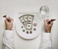 Het concept van het gelddieet. De mens houdt vork en mes. Doll Royalty-vrije Stock Fotografie
