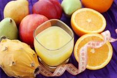 Het concept van het gewichtsverlies: diverse vruchten met glas vers gedrukt sap stock fotografie