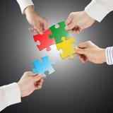 Het concept van het teamwerk, de raadsels van de Handengreep verbindt elkaar aan gr. Royalty-vrije Stock Afbeelding