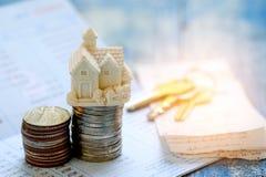 Het concept van huisbesparingen, Huismodel en muntstukken op boekbank met k Royalty-vrije Stock Fotografie