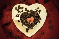 Het concept van koffie klatsch Java Het hart vormde witte kop die met geroosterde koffiebonen wordt gevuld uitstekende filter Royalty-vrije Stock Fotografie
