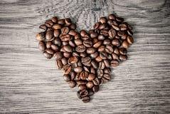 Het concept van koffiebonen op houten lijstachtergrond Stock Fotografie