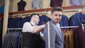 Het concept van het mensenkostuum De verkoper helpt de koper een kostuum in de kledingsopslag kiezen stock videobeelden