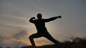 Het concept van mensenvechtsporten mannelijke strijdersmonnik het praktizeren kungfu silhouet van een mens bij zonsondergang bela stock videobeelden