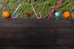 Het concept van het nieuwjaar De Kerstmisachtergrond van mandarijnenmandarins op spar vertakt zich met suikergoedriet, giftdoos,  Stock Foto's
