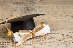 Het concept van het onderwijs Graduatiehoed met gouden leeswijzer, rol op houten lijst Wet concep- met exemplaarruimte voor stock afbeelding