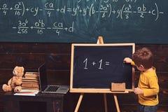 Het concept van het onderwijs Weinig jongen die vergelijking op bord oplossen Peuter opleiding voor slim jong geitje royalty-vrije stock foto's
