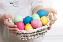 Het Concept van Pasen Een vrouw houdt mand met kleurrijke gekleurde eieren voor godsdienstige Pasen-vakantie Paaseieren in Mand Stock Afbeeldingen
