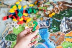 Het concept van het raadsspel met het vraagteken van de handholding Om spel hard te kiezen stock foto