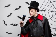 Het Concept van vampierhalloween - het Portret van knappe Kaukasische Vampier geniet van drinkend bloedige rode wijn stock foto