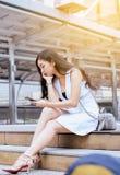 Het concept van het werkloosheidsprobleem, Aziatische mooie vrouw beklemtoonde en depressie van het werk terwijl openlucht zitten stock foto