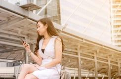 Het concept van het werkloosheidsprobleem, Aziatische mooie vrouwenverbinding Internet vindt nieuwe baan op celtelefoon terwijl o stock afbeelding