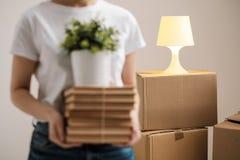 Het concept zich verhuizing en het bewegen aan een nieuw huis Het close-up, vrouwelijke handen houdt een stapel van boeken en een stock afbeeldingen
