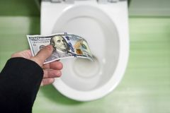 Het concept zinloos afval van geld, verlies, nutteloos afval, grote waterkosten, 100 Dollarsrekeningen spoelde in een toiletkom stock foto
