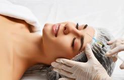 Het concepten dienen het jonge donkerbruine vrouw van de plastische chirurgieschoonheid gezicht en de arts handschoen met spuit i Stock Afbeeldingen
