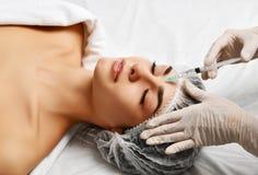 Het concepten dienen het jonge donkerbruine vrouw van de plastische chirurgieschoonheid gezicht en de arts handschoen met spuit i Royalty-vrije Stock Afbeelding