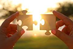 Het conceptenbeeld van een vrouw overhandigt holding twee stukken van een raadsel voor de zon zonsondergangtijd met lensgloed de  stock fotografie