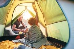 Het conceptenbeeld van familielisure De vader en de zoon treffen voor het kamperen in berg voorbereidingen, drinken thee in tent royalty-vrije stock foto