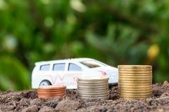 Het conceptenmuntstukken van de geldgroei in grond Verzamel geld om een auto te bouwen Stock Foto