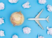 Het conceptenstuk speelgoed van de wereldreis vliegtuig en Bol in Document Wolkenhemel stock afbeeldingen